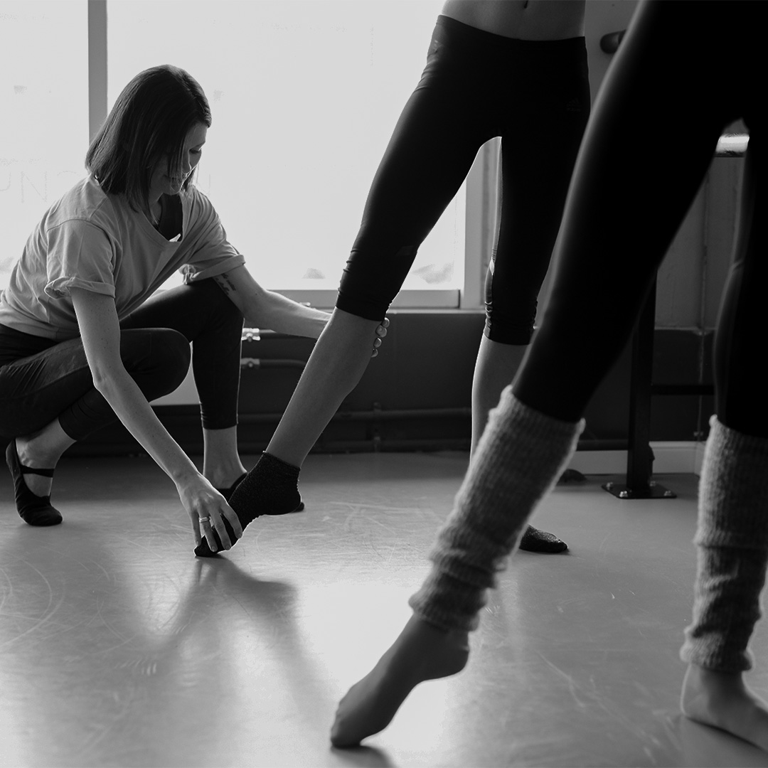 Instructor adjusting dancer's form